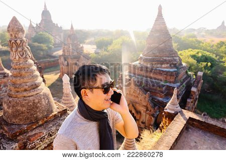 Young Man Talking On The Phone In Rural And Temple Pagoda Area - Can Indicate Good Signal Of Telecom