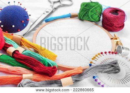 Colorful threads and embroidery hoop with fabric, closeup
