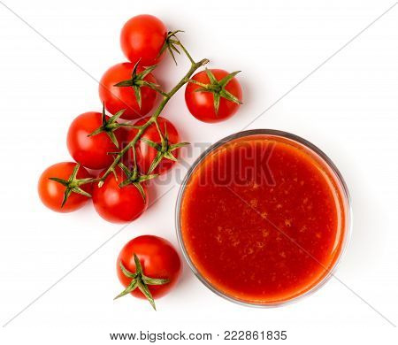 Tomato juice in a glass and a branch of red tomatoes on a white background. The view from the top.