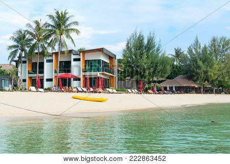 KO LIPE, THAILAND - APR 2017: Seaview hotel with sunbeds and umbrellas on a clean tropical sand beach