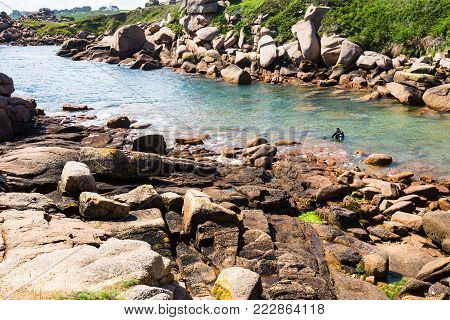 travel to France - diver in Ploumanac'h site of Perros-Guirec commune on Pink Granite Coast of Cotes-d'Armor department in the north of Brittany in sunny summer day