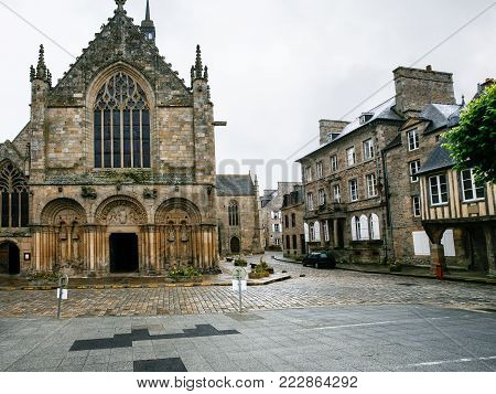 travel to France - Basilica of St Saviour on square Place Saint-Sauveur of Dinan town in rain