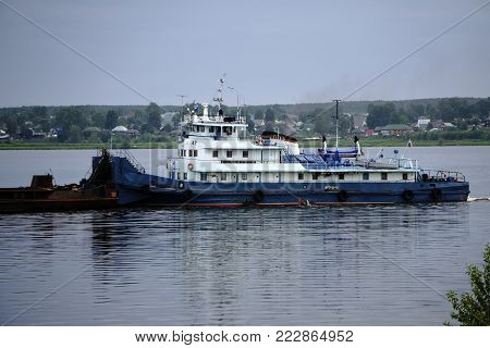tug pushing a barge on the river