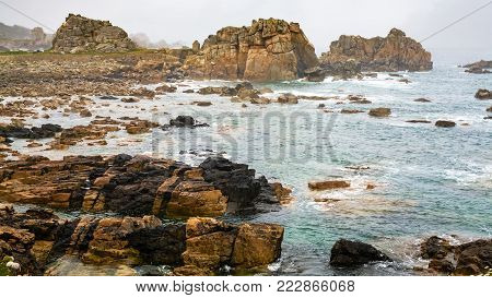 travel in France - view of rocky shore of Gouffre gulf of English Channel near Plougrescant town of the Cotes-d'Armor department in Brittany in summer rainy day