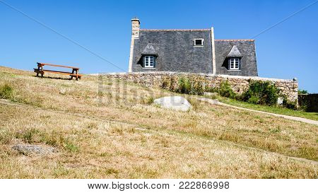 travel to France - bench on hill near country houses in Brehat commune on Ile-de-Brehat island in Cotes-d'Armor department of Brittany in summer sunny day