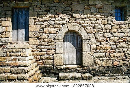 travel to France - front view of old stone country house in Brehat commune at Ile-de-Brehat island in Cotes-d'Armor department of Brittany in summer sunny day