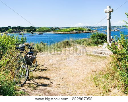 travel to France - tourist bicycle at viewpoint near Celtic cross on Ile-de-Brehat island in Cotes-d'Armor department of Brittany in summer sunny day