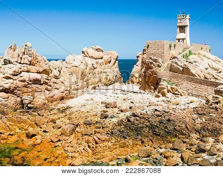 travel to France - Paon Lighthouse (Phare du Paon) on pink granite coast of Ile-de-Brehat island in Cotes-d'Armor department of Brittany in summer sunny day