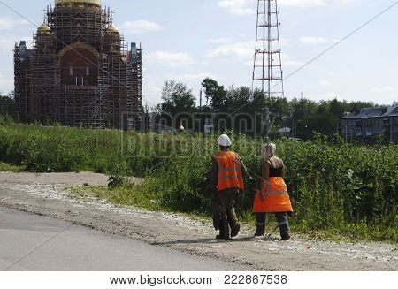 two workers in orange overalls are back from lunch .