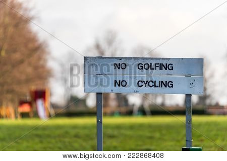 No Golfing and No Cycling sign post. Not allowed to play in this area, there were signs: Do not play golf and do not cycle.
