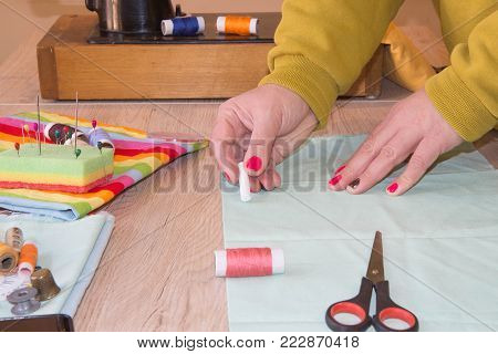 Woman dressmaker drawing tailor pattern with chalk for a clothing on the table. The outline on the fabric painted chalk. Garment industry, tailoring concept