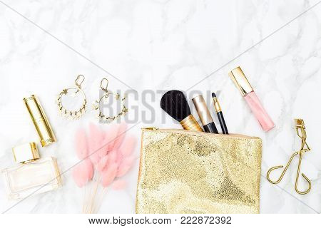 Makeup and accessories gold and pink for girls on the table.Copy space