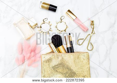 Makeup and accessories flat lay. Gold and pink styled stock