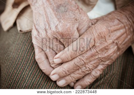 Hands Asian elderly woman grasps her hand on lap, pair of elderly wrinkled hands in prayer sitting alone in his house, World Kindness older and Adult care,  Mother day people concept