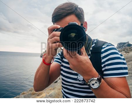 photographer male tourist with a digital camera and large lens looking forward