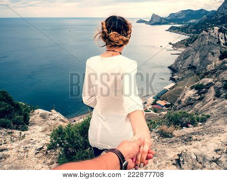 guy follows a beautiful girl holding her hand in the tourist journey to the edge of the mountain against the sea. Young slender girl in a white dress in summer resting