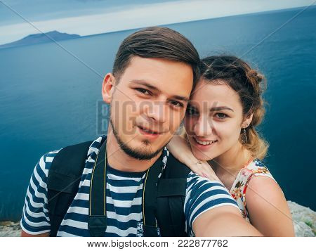 happy couple in love girl and her boyfriend doing a selfie on a trip to holiday at the sea. A very happy girl smiles and the guy with the beard happy and together