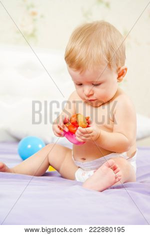 Little girl playing with toy sitting on bed