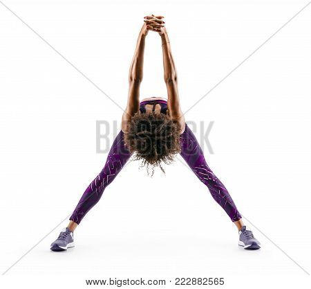 Fit girl warming up. Full length of young african girl in sportswear stretching her arms on white background. Stretching and motivation