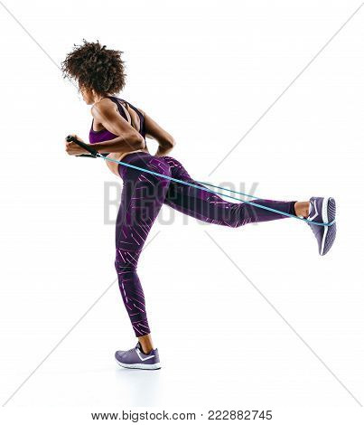 Sporty girl doing exercises with resistance band isolated on white background. Back view. Strength and motivation.