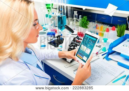 Young attractive woman scientist using tablet computer in the scientific chemical laboratory