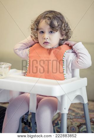 A two-year-old naughty child tries to take off his bib while eating. Baby girl is sitting on a high chair.