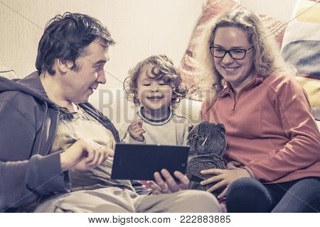 Happy family with baby girl sitting on a couch and using a digital tablet. Cheerful two-year-old child looks electronic device at home. Father and mother show something to their joyful little child on the tablet screen.