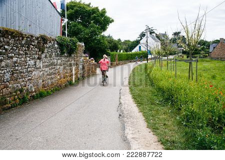 ILE-DE-BREHAT, FRANCE - JULY 4, 2010: tourists on bicycles on street in Brehat commune. Ile-de-Brehat is island and commune located near Paimpol town, a mile from the northern coast of Brittany