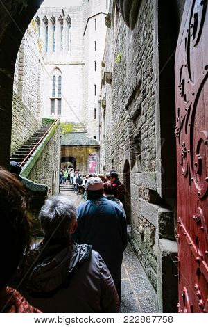LE MONT SAINT-MICHEL - JULY 5, 2010: turn of tourists to the entrance in Saint Michael's Abbey. Le Mont Saint-Michel is island commune in Normandy, first monastic on the mount was built in 8th century