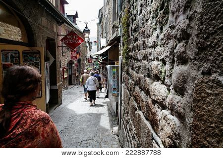 LE MONT SAINT-MICHEL - JULY 5, 2010: tourists walk along narrow street in Saint Michael's Castle. Le Mont Saint-Michel is an island commune in Normandy