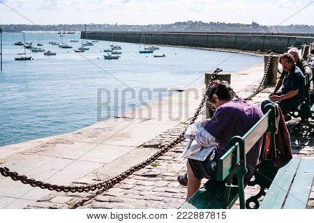 SAINT-MALO, FRANCE - JULY 5, 2010: citizens on Esplanade Robert Surcouf in Saint-Malo town near city gate Porte de Dinan. Saint-Malo is walled port city in Brittany on the English Channel coastline