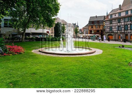 COLMAR, FRANCE - JULY 11, 2010: people near fountain on Place des Unterlinden in Colmar. Colmar is the third-largest commune of Alsace region, town is considers itself as the capital of Alsatian wine