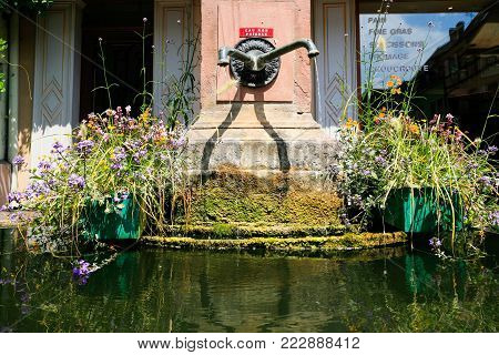 RIQUEWIHR, FRANCE - JULY 11, 2010: old water spring in Riquewihr city. Riquewihr is commune in Alsace Wine Route region, the town belongs to the association The most beautiful villages of France