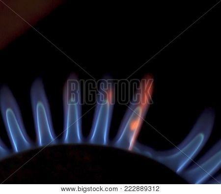 Plate. Kitchen stove. A modern kitchen stove with a burning combustible flame. Taken at night, close-up.
