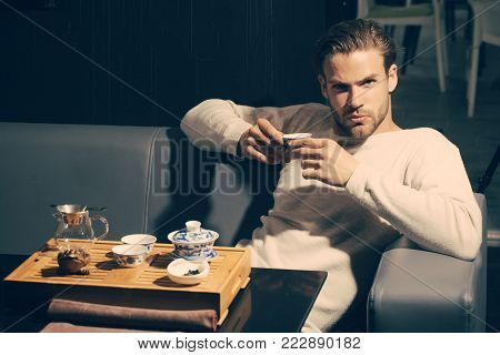 Man drink tea on sofa in cafe. Tea party, ceremony, time. Brew tea concept. Relaxation, lounge, relax. Beverage, food, cuisine.