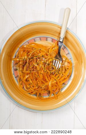 spiralized butternut squash with home made salad dressing on a plate