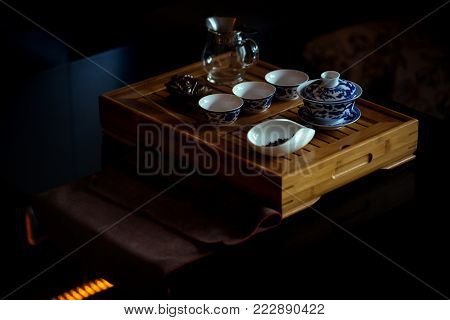 Tea set and lucky money toad on wooden tray. Teapot, cups and feng shui symbol served in restaurant. China tradition, culture. Tea party, ceremony, time. Beverage, food, cuisine.
