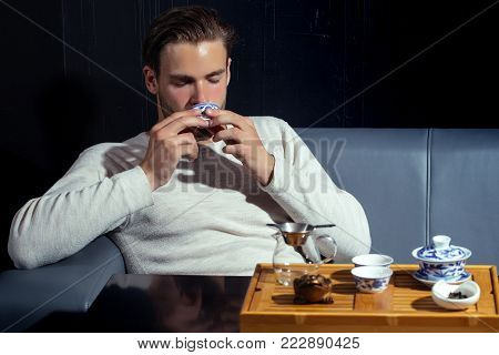 Relaxation, lounge, relax. Man drink tea on sofa in cafe. Beverage, food, cuisine. Brew tea concept. Tea party, ceremony, time.