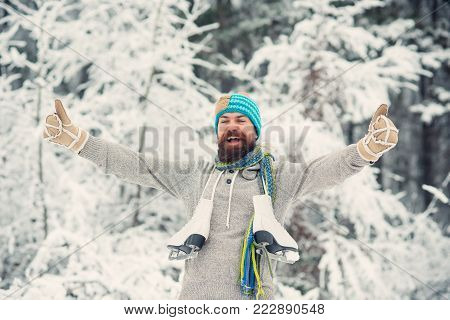 Bearded Man Smoking Cigarette With Skates In Snowy Forest.