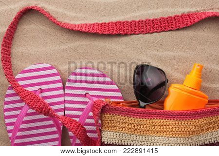 Beach accessories. Bag, sunglasses and flip flops. With a place for your text. View from above