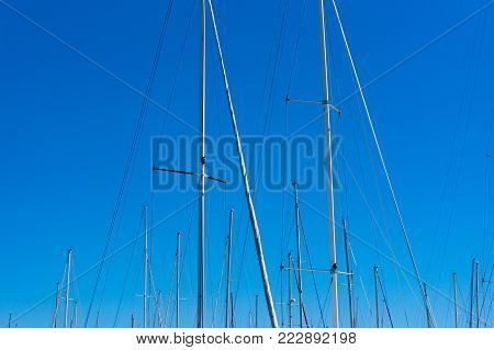 Abstract nautical, marine background of yacht's masts with blue sky on the background. Travel, adventure and exploration scene