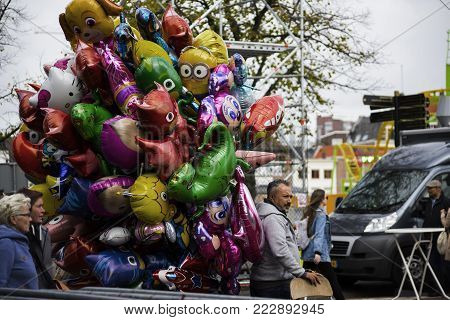 Leiden, The Netherlands 3 October 2017. a balloon vendor with a big pile of floating air balloons standing on the corner of the street.