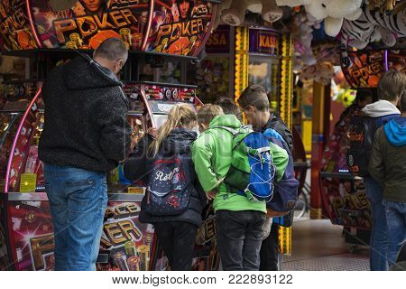 Leiden, The Netherlands 3 October 2017, A group of children and there father gathered around a attraction fairground coin gambling machine.