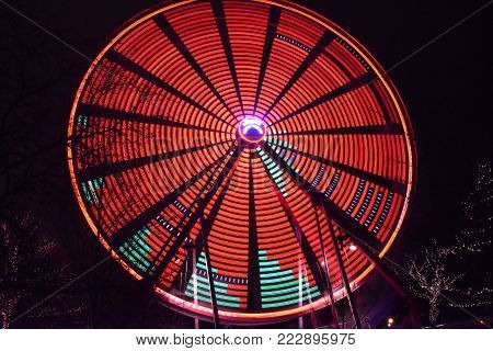 Red Light Illuminated Spinning Ferris Wheel in Motion moving at night