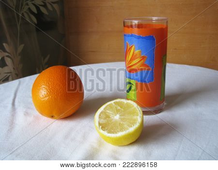 Still life. Orange, lemon, glass on a white tablecloth. Attractively look citrus and colorful glass on the tablecloth, casting shadows and reflecting.