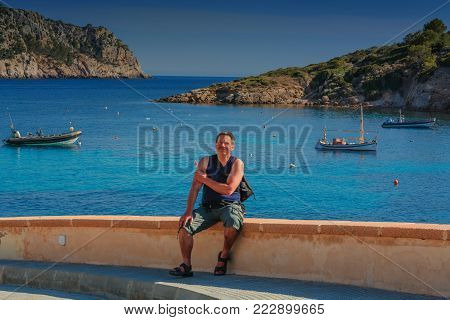 Man sitting on a wall overlooking the side of the sea and relaxing. Concept of freedom. In the background a rock with a rusty ship anchor. Mallorca, Spain.