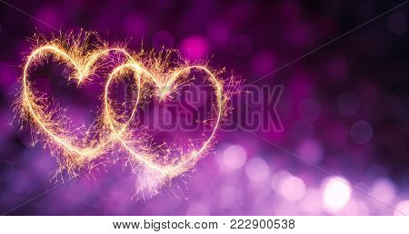 Beautiful Festive violet purple background with two glowing gold hearts. Holiday greeting and invitation card with copy space. Web banner or flyer for Valentine's Day, wedding, birthday and anniversary
