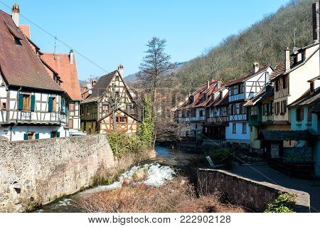 French traditional half-timbered houses and La Weiss river in Kayserberg village in Alsace, France. Outdoors horizontal colored image. Blue sky cloudless background.