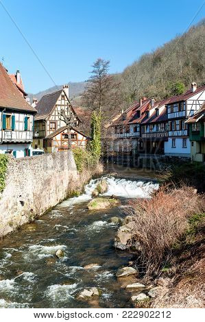 French traditional half-timbered houses and La Weiss river in Kayserberg village in Alsace, France. Outdoors vertical  colored image. Blue sky cloudless background.