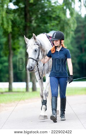 Young cheerful teenage redhead lady equestrian leading her favorite gray horse from training. Vibrant colored outdoors vertical summertime image.